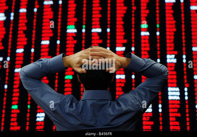Stock Trader Stood in Front of a Large Display of Stock Prices - Stock Image