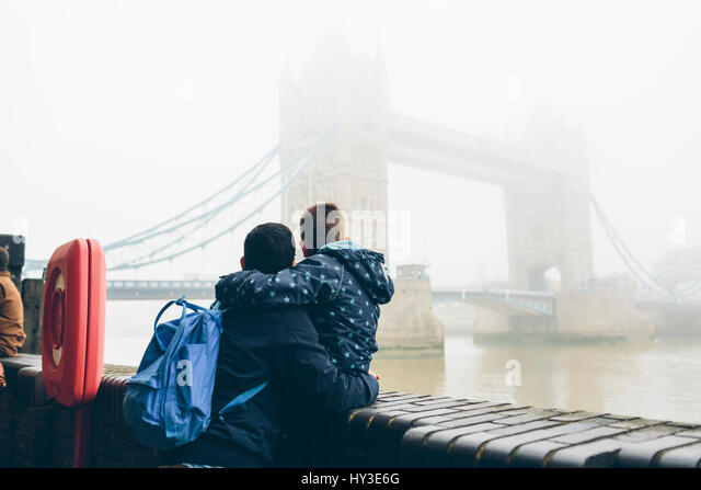 UK, England, London, Mid adult man holding boy (8-9) while looking at Tower Bridge in fog - Stock Image