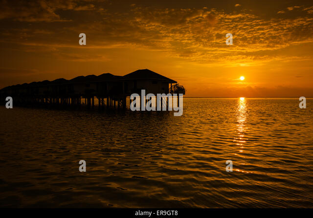 Maldives sunset with water villas silhouette and cloudy sky - Stock Image