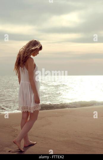 Blonde woman walking on beach looking down - Stock-Bilder