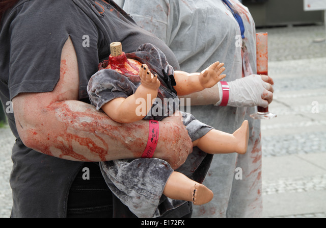 Close up of a doll without head and with theater blood, held by a woman at the ombie walk in Prague 2014 - Stock Image