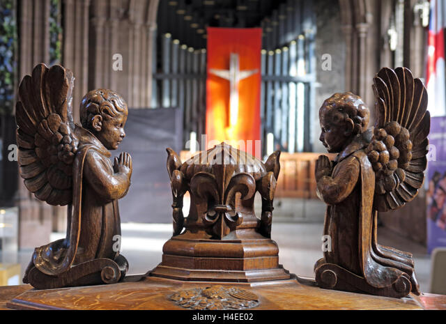 Crucifix and organ pipes behind font angels,Manchester cathedral,England,UK - Stock Image