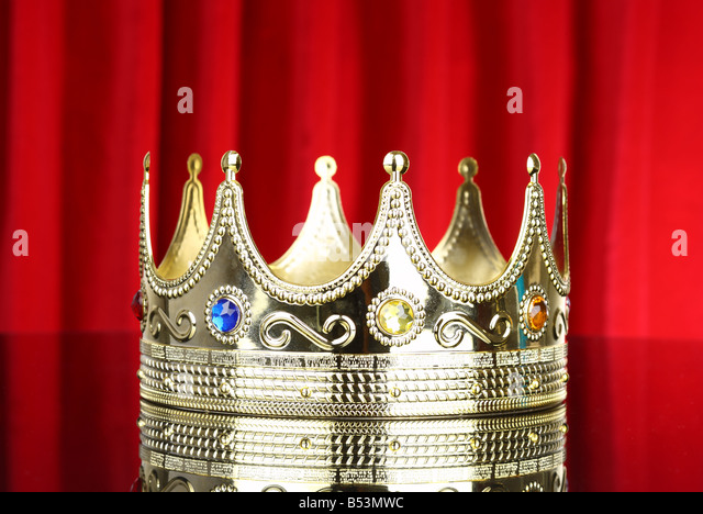 Crown with red curtain background - Stock Image