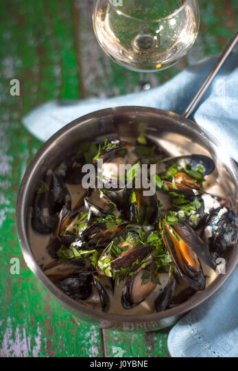 Mussels in sash in saucepan on boards - Stock Image