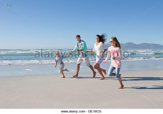 Happy family running on sunny beach - Stock Image