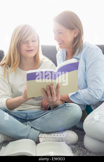 Mother assisting daughter in homework at home - Stock Image