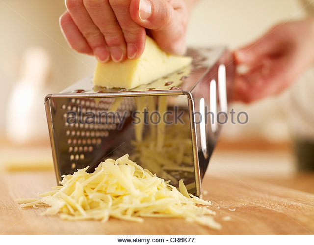 Woman shredded cheese with grater - Stock Image