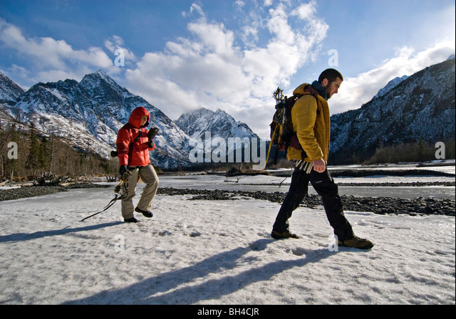 Two young ice climbers walk across a snowy river, with gear in hand, on their way to an afternoon ice climb in Echo - Stock Image