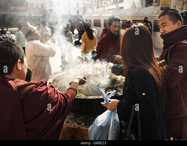 Pilgrims at the Boudhanath Stupa burning incense and praying. - Stock Image