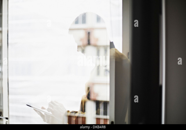 Reflection of businessman using digital tablet - Stock Image