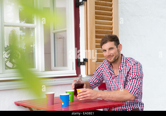 Mid adult man at table pouring soft drink - Stock Image