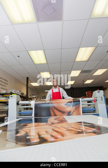 Worker taking printouts at printing press - Stock Image