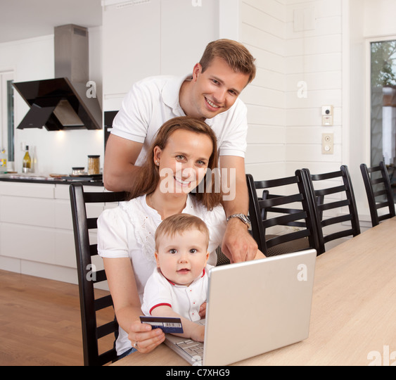 Happy family looking at the camera with a smile making an online purchase - Stock Image