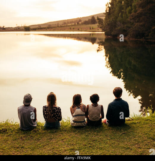 Rear view image of group of young friends sitting in a row by a lake and looking at a beautiful landscape view. - Stock Image