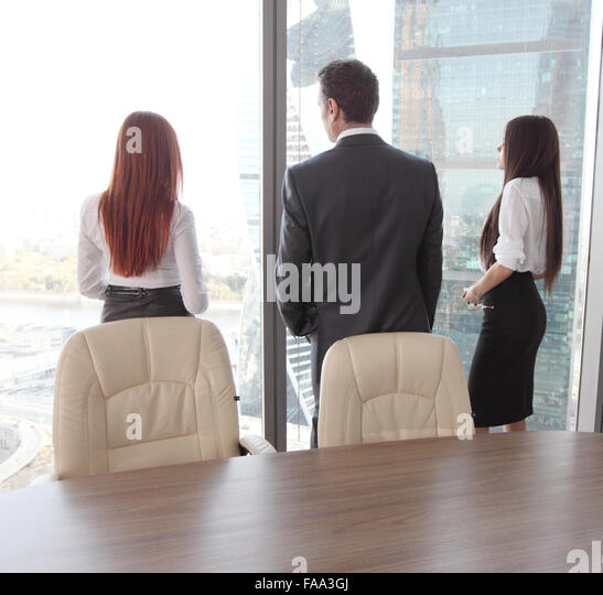 Rear view of business people looking at window - Stock-Bilder
