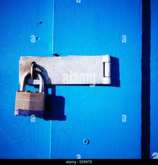 A locked padlock on a blue wooden door. - Stock Image