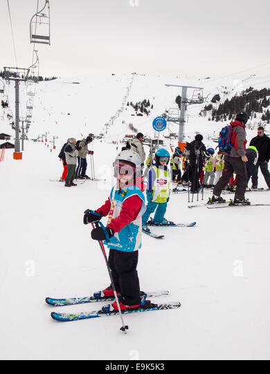 small girl on skis wearing ski clothes and helmet waiting  for a skiing lesson at a ski school collection point - Stock Image