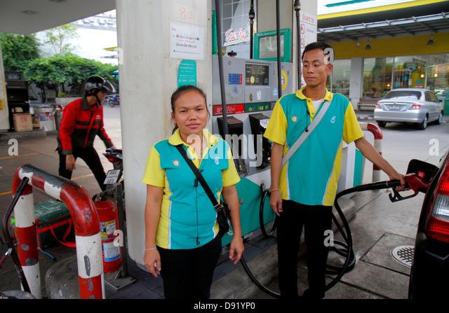 Bangkok Thailand Pom Prap Sattru Phai Lan Luang Road business Petronas petrol gas station Asian woman man employees - Stock Image