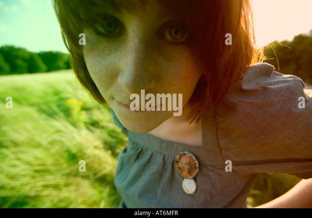 Red headed woman in corn field, portrait - Stock Image