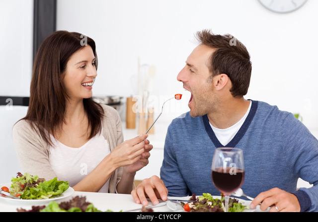 Pretty woman giving a tomato to her boyfriend while having lunch - Stock-Bilder