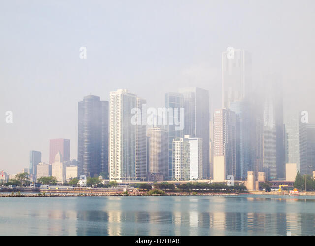 A view of the Chicago skyline, obscured by a heavy advection fog off Lake Michigan, as seen from Navy Pier. - Stock Image