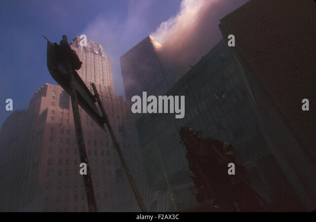 Fire fighter at base of burning WTC 6 following the North Tower (WTC 1) collapse. Dense dust and smoke block sunlight. - Stock-Bilder