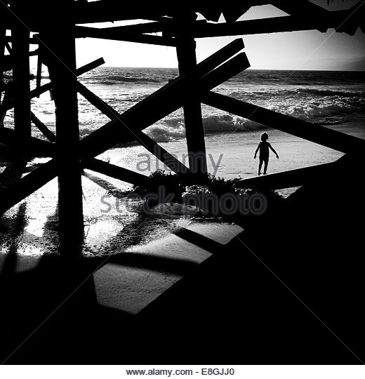 silhouette of boy walking under the pier, Santa Monica, California, America, USA - Stock Image