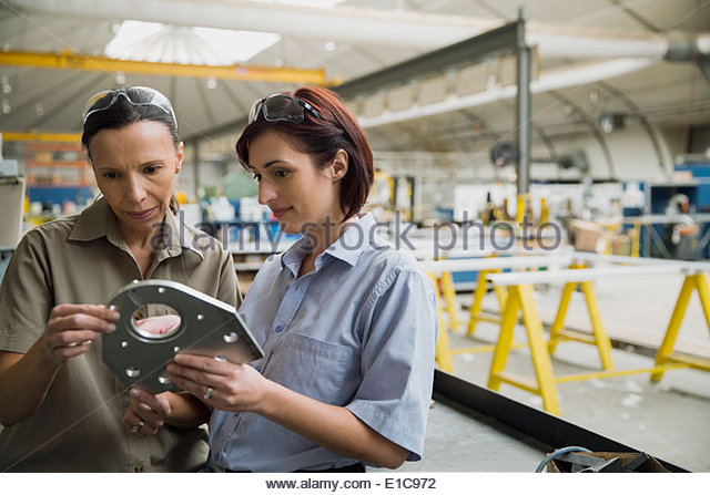 Workers examining metal part in manufacturing plant - Stock Image