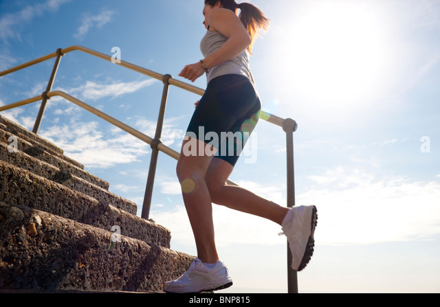 Profile of a woman running up steps, low angle view - Stock-Bilder