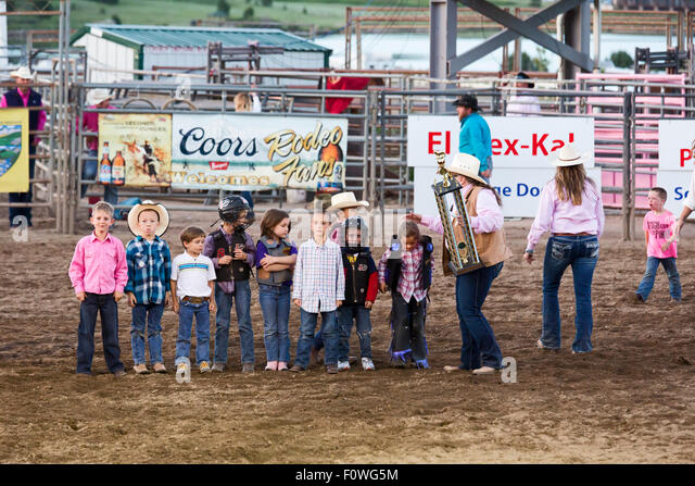 Estes Park, Colorado - An official at the Rooftop Rodeo holds a trophy for the Mutton Bustin' winner. - Stock Image