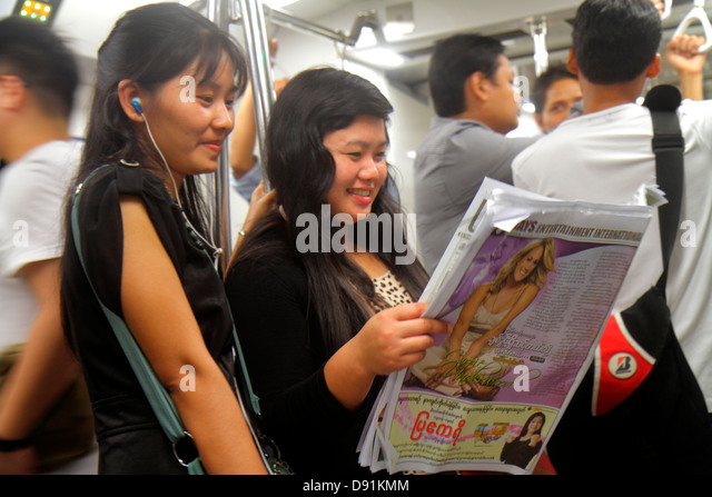 Singapore MRT East West Line subway train cabin public transportation riders commuters Asian woman standing reading - Stock Image