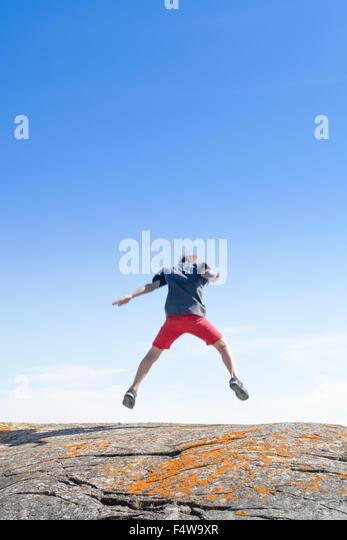 Sweden, Uppland, Runmaro, Barrskar, Boy (6-7) jumping on rock, Rear view - Stock Image