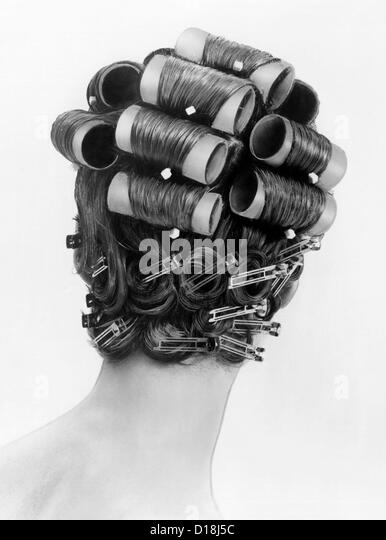 1960s bouffant hair styles were created with big rollers on top of the head and pin curls to create a soft flip - Stock Image