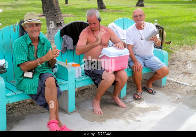 Miami Beach Florida Lummus Park Hispanic man senior making music rhythm clapping hands ice chest drum thermos shaker - Stock Image