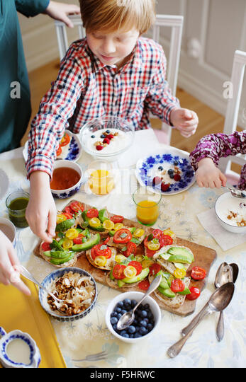 Sweden, Mother with two children (2-3, 10-11) eating breakfast - Stock Image