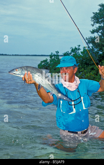 proud male angler holds 9lb trophy bonefish wading in shallow  water Bahamas  Andros Island - Stock Image
