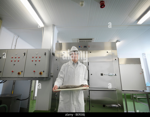 Food Worker With Fish On Board - Stock Image