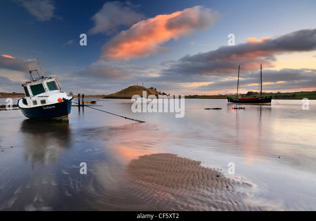An old fishing boat moored in Alnmouth estuary at low tide. - Stock Image