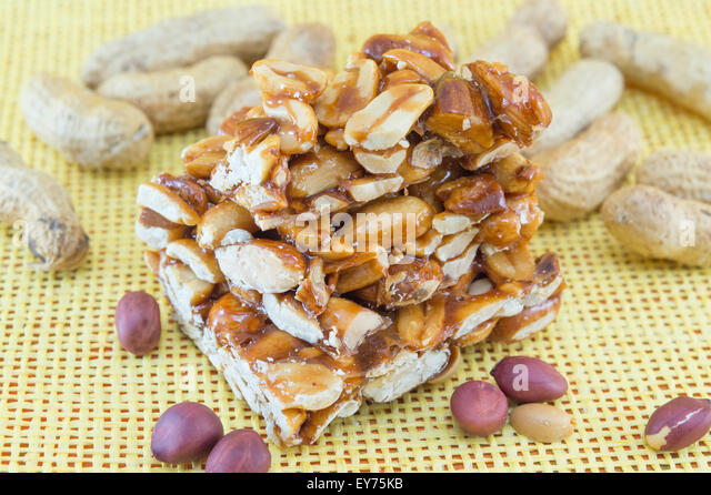 Honey bar with peanuts almonds and hazelnuts surrounded by bunch of roasted and raw peanuts on yellow background - Stock Image