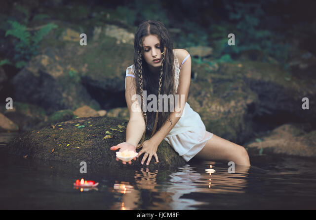 Beautiful water nymph in forest stream with floating candles . Fantasy and romantic concept - Stock Image