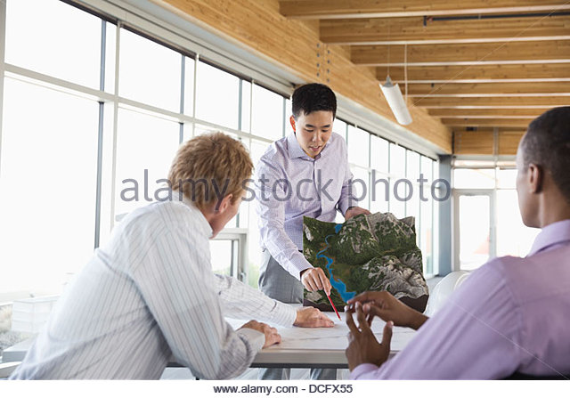 Engineers reviewing landscape model and blueprints - Stock Image