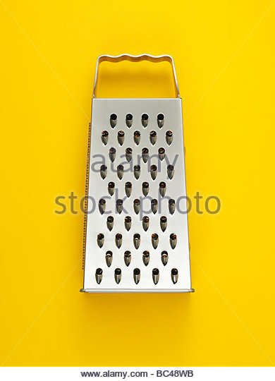a cheese grater photographed on a yellow background overhead - Stock-Bilder