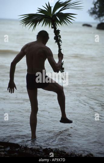 Jamaica Port Antonio Dragon Bay Beach man palm frond umbrella dancing water - Stock Image