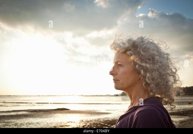 Mature woman enjoying beach - Stock Image