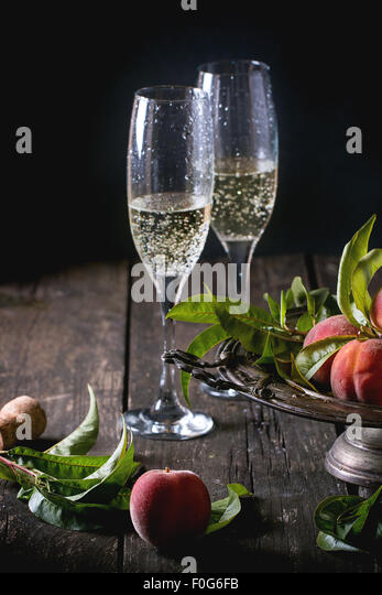Peaches on branch with champagne - Stock Image