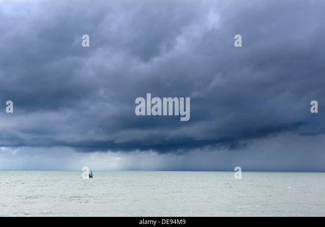 Small dinghy sailing towards a storm off the coast of the seaside village of Aberaeron, Ceredigion, Wales, UK - Stock Image