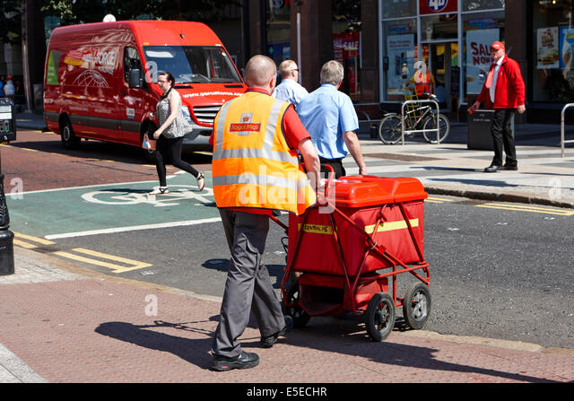 royal mail postman wheeling a cart of mail Belfast city centre - Stock Image