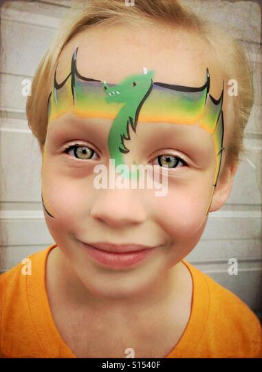 A young girl with a dragon painted on her face. - Stock Image