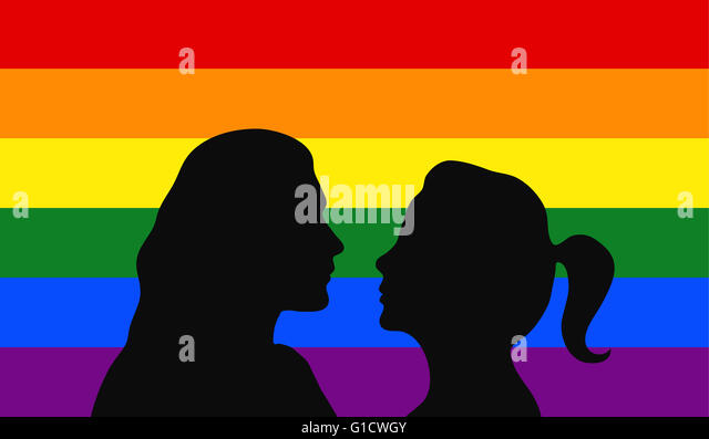 Lesbian couple in front of rainbow flag. - Stock Image