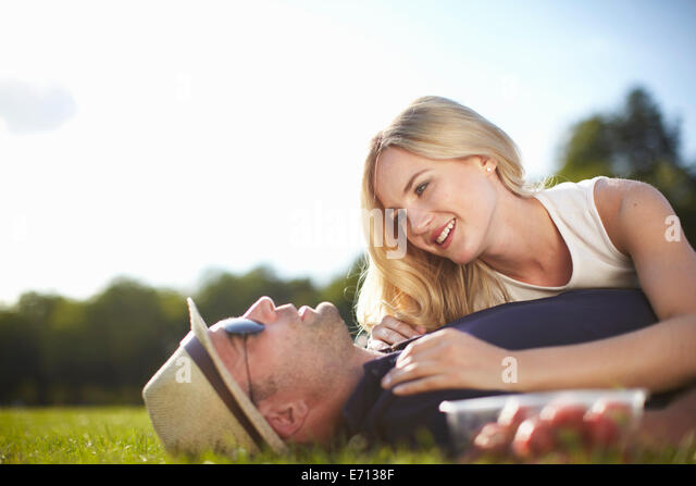 Couple lying and chatting in park - Stock-Bilder